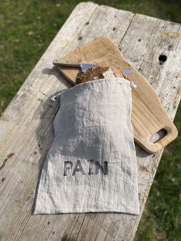sac à gros pain en lin sur la table en bois avec un couteau et une planche à découper en bois